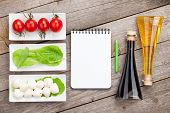 Tomatoes, mozzarella and green salad leaves on wooden table background with notepad for copy space