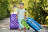 The little girl travels with big suitcases