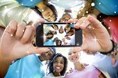 image of huddle  - Hand holding smartphone showing friends forming huddle - JPG