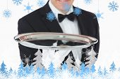 Smiling man holding a silver tray against snowflakes and fir trees