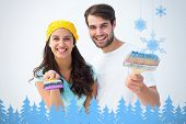 Happy young couple painting together against snowflakes and fir trees in blue