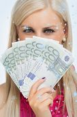 Green eyed woman holding 100 euros banknotes against snow falling