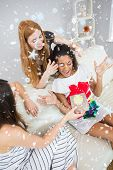 Cheerful young women surprising friend with a gift against snow falling