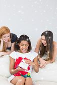 Cheerful young women surprising friend with a gift against night sky