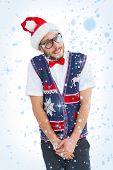 Geeky hipster in santa hat against snow falling