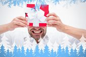 Stressed man holding a present against frost and fir trees