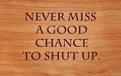 Never miss a good chance to shut up - an old saying on wooden red oak background