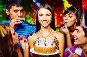 Portrait of joyful girl with birthday cake looking at camera at party with her friends near by