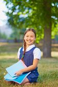 Happy schoolgirl with copybooks looking at camera in park