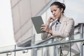 Beautiful young businesswoman using digital tablet at office railing