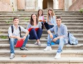 Group of smiling students sitting on a staircase