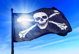 stock photo of skull crossbones flag  - Pirate skull and crossbones flag waving on the wind - JPG
