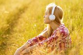 Girl With Headphones Sitting In The Grass