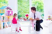 picture of doll  - Happy family young father and his little daughter cute curly toddler girl wearing a dress playing together with doll house having toy tea party in a white sunny nursery - JPG