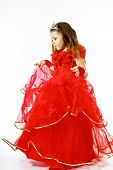 Cute Little Princess Dressed In Red  With Crown On Her Head Posing In Studio