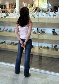 Young woman in jeans window shopping
