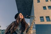 Beautiful Young Woman With Her Saxophone