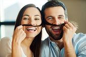 pic of love making  - Beautiful young loving couple bonding to each other and smiling while making a fake mustaches from her hair - JPG