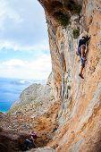 Young man lead climbing on cliff near sea