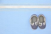 Baby shoes on blue polka dots background