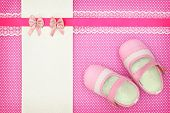 Baby shoes and blank banner on polka dots background