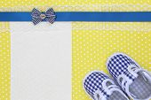 Baby shoes and blank banner on yellow polka background