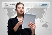 Portrait of a woman using a digital tablet in front of a world map