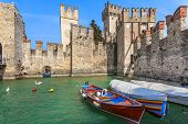 Boats on lake Garda and Scaliger medieval castle in town of Sirmione, Italy.