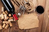 Red wine, corks, corkscrew and piece of paper for copy space on wooden table background