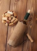 White wine bottle, corks and corkscrew over wooden table background. Top view