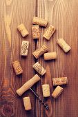 Wine corks and corkscrew over rustic wooden table background. Retro toned