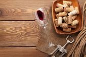 Red wine glass, corks and corkscrew on wooden table background with copy space