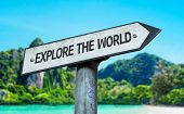 Explore the World sign with a beach on background