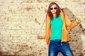 Young stylish girl in the city. Brick wall background. Youth fashion. Hip-hop style.