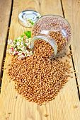 stock photo of buckwheat  - Buckwheat in a glass jar and on the table - JPG