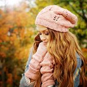 Sunny autumn portrait of a cute young woman dressed in pink knitted hat and gloves.