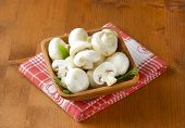 white champignon mushrooms, served in the wooden bowl with fabric linen