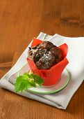 side view of smooth chocolate cupcake in the red paper basket, served on the plate with fabric linen