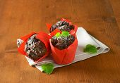 selection of three delicious chocolate cupcakes in the red paper baskets