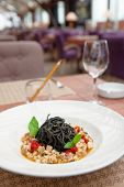 Black squid ink pasta with seafood on restaurant table
