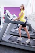 young woman doing exercises on treadmill