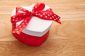 Gift In The Form Of Heart Tied With Red Ribbon With A Bow On Wooden Board