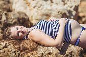Pregnant woman on the rocky shore near the sea.