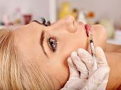 Doctor woman giving botox injections. Syringe in hand close-up