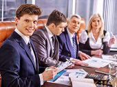 Happy group business people in office. In the foreground handsome businessman