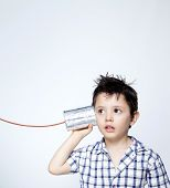 image of tin can phone  - Child using a can as telephone against gray background - JPG