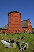 stock photo of silos  - Restored horse drawn plows are on display in from of a wood stave silo and red hip roof barn - JPG