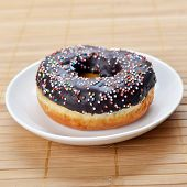 image of icing  - sweet donut with chocolate icing and colored sugar on wooden background - JPG