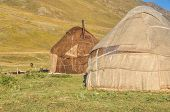 stock photo of yurt  - Nomadic settlements with yurts on green grasslands in Kyrgyzstan - JPG