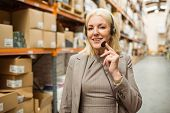 Smiling woman wearing a headset in a large warehouse